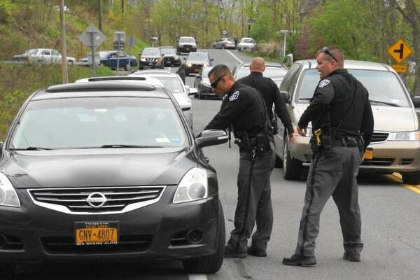 "Law enforcement officials speak to a driver on the road to Schodack Island State Park in Schodack Landing on Saturday, April 29, 2017, where police responded to alleged fights at an concert event called ""Rumble in the Jungle."" (Martin E. Miller/Special to the Times Union)"