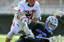Darien Logan McGovern maintains control of the ball under pressure from New Canaan Andrew Bauersfeld in a FCIAC boys lacrosse game at New Canaan High School Dunning Field in New Canaan, Conn. on April 29, 2017. Darien defeated New Canaan 11-8.