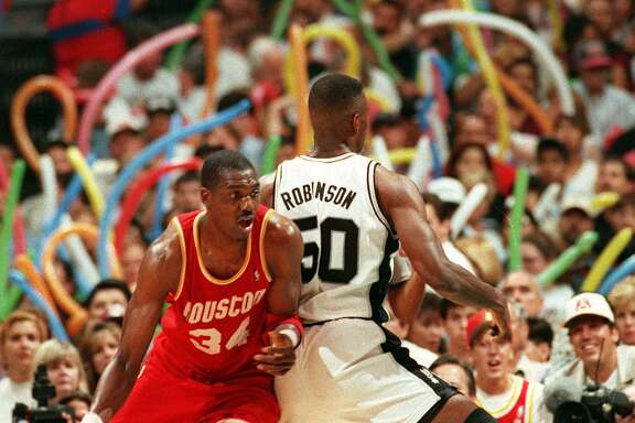 """FILE -- DREAM SHAKE -- Hakeem Olajuwon is pictured here doing the famous """"dream shake"""" which caught David Robinson off guard during the playoffs at the Alamodome on 5/24/1995. SPRUS V. ROCKETS -- Photo by Doug Sehres / Staff"""