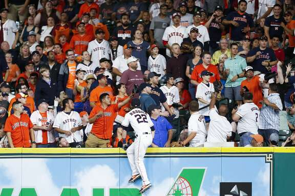 Houston Astros left fielder Josh Reddick (22) goes into the stands as he attempts to get an unreachable home run during the eighth inning as the Houston Astros take on the Oakland Athletics at Minute Maid Park Saturday, April 29, 2017 in Houston. ( Michael Ciaglo / Houston Chronicle)