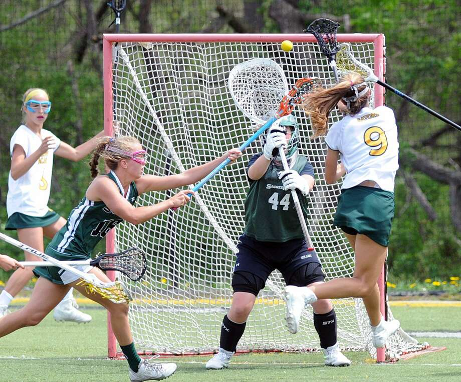 Greenwich Academy's Karina Schulze scores against Sacred Heart goalie Madeline McLain during GA's 11-8 victory Saturday at Sacred Heart in Greenwich. Photo: Bob Luckey Jr. / Hearst Connecticut Media / Greenwich Time
