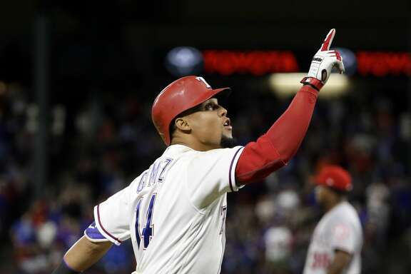 Texas Rangers' Carlos Gomez points skyward as he approaches the plate after hitting a two-run home run off of Los Angeles Angels relief pitcher Jose Valdez, rear, during the seventh inning of a baseball game in Arlington, Texas, Saturday, April 29, 2017. Gomez hit for the cycle. (AP Photo/Tony Gutierrez)