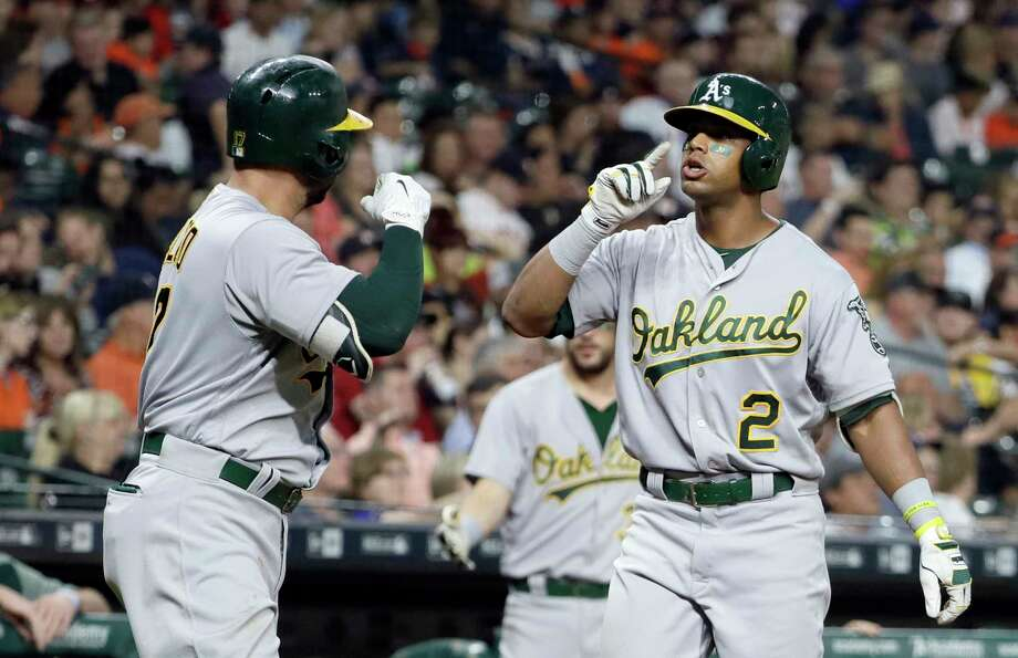 Oakland Athletics' Khris Davis (2) celebrates with Yonder Alonso after hitting a home run during the eighth inning of a baseball game against the Houston Astros on Saturday, April 29, 2017, in Houston. (AP Photo/David J. Phillip) Photo: David J. Phillip, STF / Copyright 2017 The Associated Press. All rights reserved.