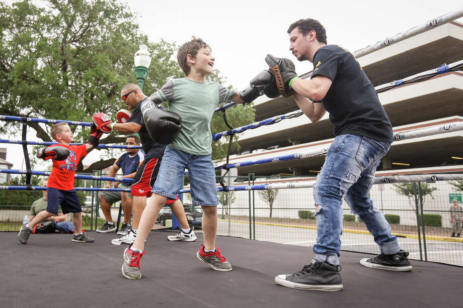 James Manriquez, a boxer that trains with Fearless Boxing Gym, shows Corbin Hornsby, 6, how to throw a punch combo during KidzFest on Saturday, April 29, 2017, in downtown Conroe. Photo: Michael Minasi, Staff Photographer / © 2017 Houston Chronicle