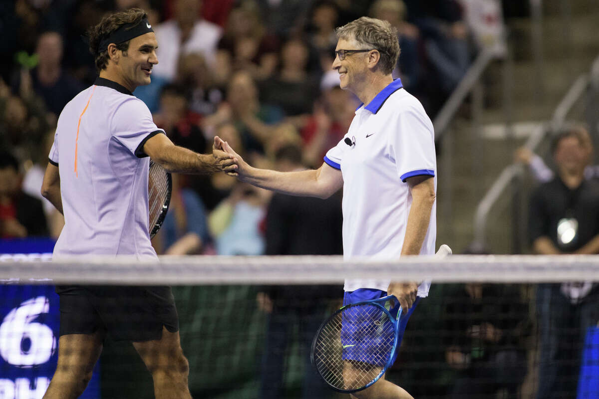 Roger Federer and Bill Gates high five during the doubles match in The Match for Africa 4 at KeyArena on Saturday, April 29, 2017. Proceeds of the match benefit the Roger Federer Foundation and its projects to help children in poverty.