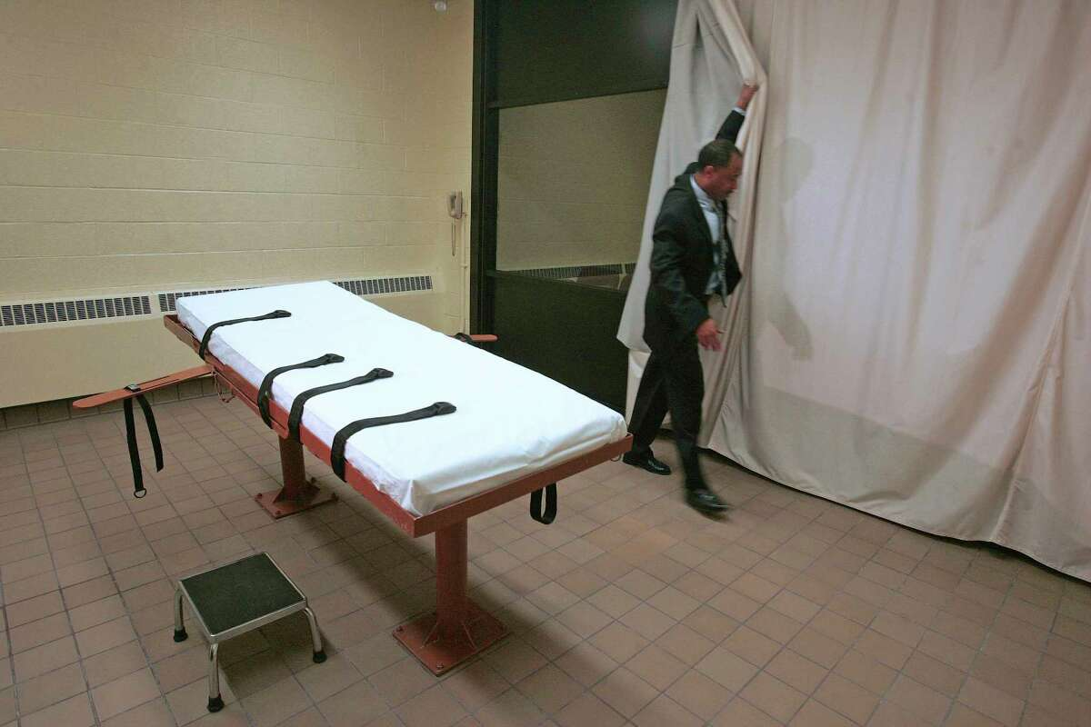 FILE ?- In this November 2005 file photo, Larry Greene, public information director of the Southern Ohio Correctional Facility, demonstrates how a curtain is pulled between the death chamber and witness room at the prison in Lucasville, Ohio. The effectiveness of midazolam has been questioned following executions in Ohio, Arizona and, in April 27, 2017, Arkansas. Condemned inmate Kenneth Williams lurched and convulsed 20 times during a lethal injection execution that began with the controversial drug. (AP Photo/Kiichiro Sato, File) ORG XMIT: NY121