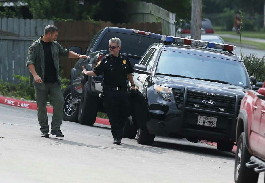Members  of the negotiating team from the San Antonio Police Department exchange a handshake after peacefully concluding a hostage situation. Photo: Kin Man Hui / San Antonio Express-News / ©2017 San Antonio Express-News