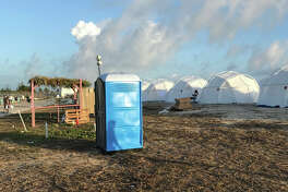 """This photo provided by Jake Strang shows tents and a portable toilet set up for attendees for the Fyre Festival, Friday, April 28, 2017 in the Exuma islands, Bahamas. Organizers of the much-hyped music festival in the Bahamas canceled the weekend event at the last minute Friday after many people had already arrived and spent thousands of dollars on tickets and travel. A statement cited """"circumstances out of our control,"""" for their inability to prepare the """"physical infrastructure"""" for the event in the largely undeveloped Exumas. (Jake Strang via AP) ORG XMIT: NY114"""