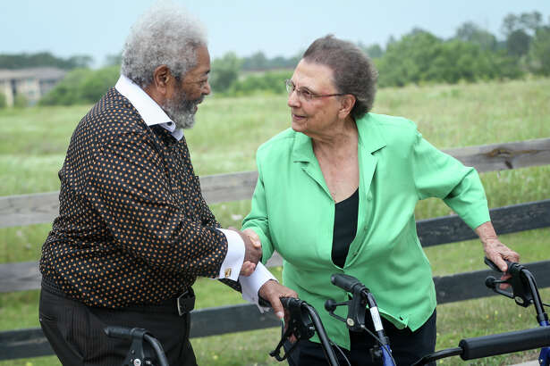 Timothy McWashington, left, and Imogene Giesinger, right, shake hands during the dedication ceremonies for Giesinger and McWashington street signs on Saturday in Montgomery.
