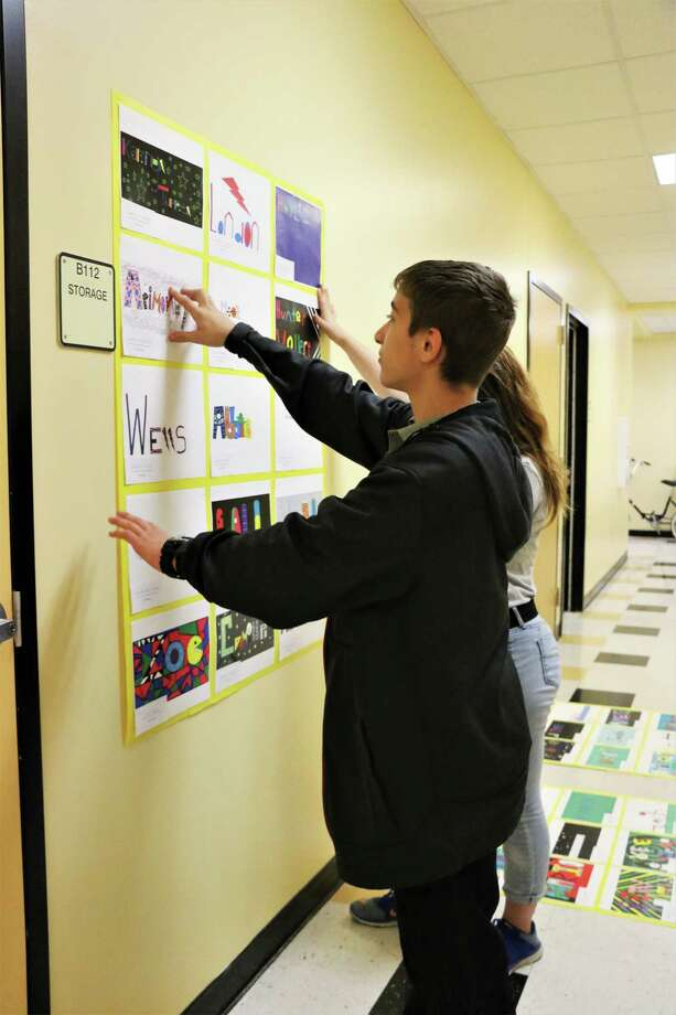 Graphic arts students arrange some of the many projects they accomplished this year on one of the walls of Liberty Middle School. Photo: David Taylor