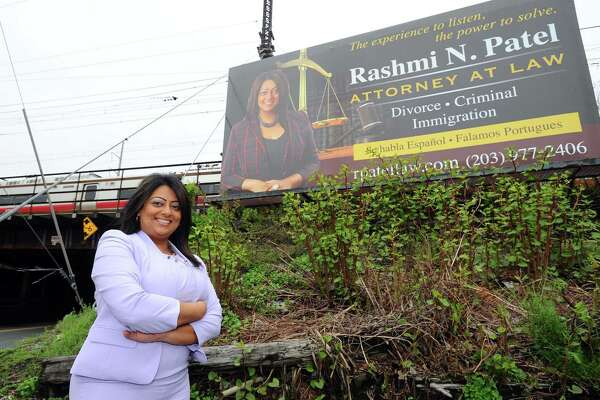 Immigration attorney Rashmi Patel poses for a photo in front of one of several billboards in Stamford.