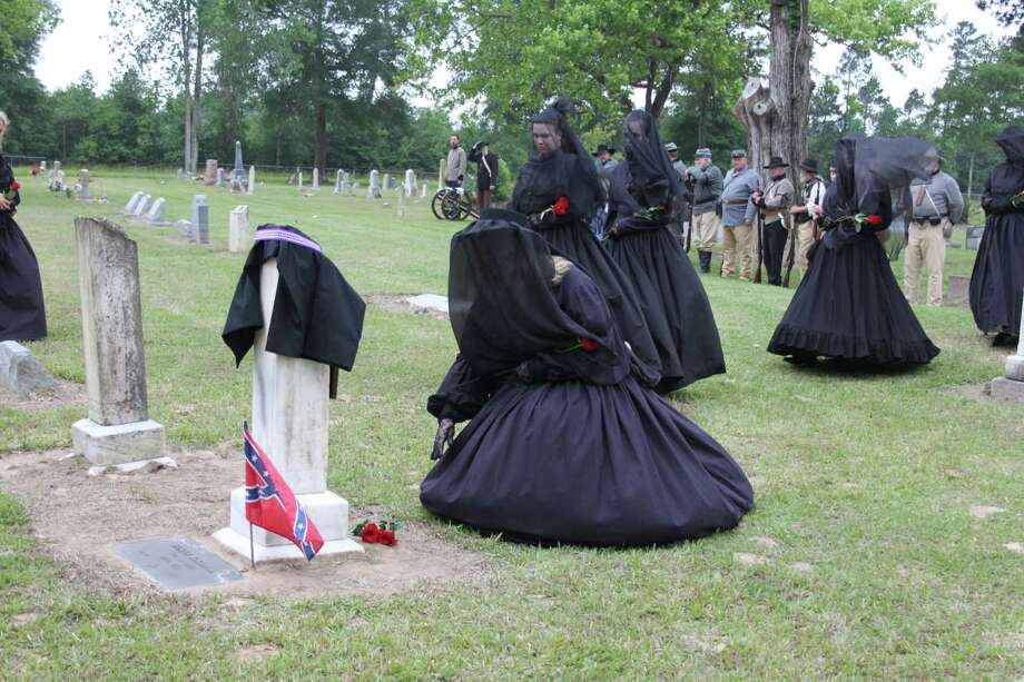 A group of women dressed in black veils leave roses on the graves of James Kirkham and David Crockett Ellington as a sign of respect in the Black Rose Ceremony. The ceremony is named in honor of Rose O'Neal Greenhow who served the Confederacy as a spy during the American Civil War. Photo: Jacob McAdams