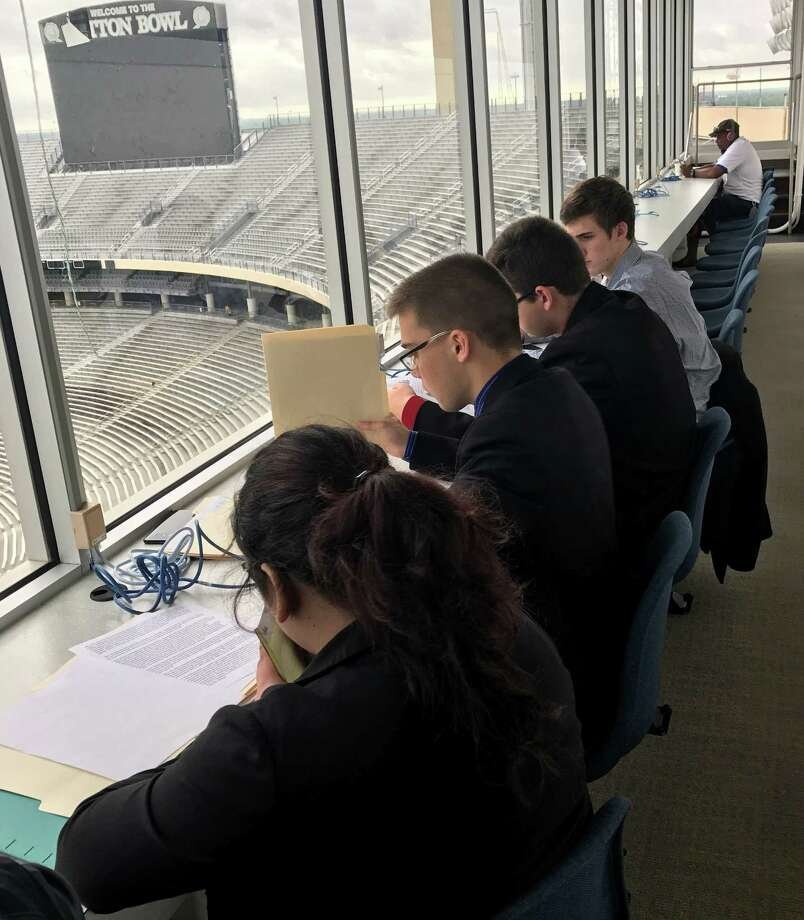 Dayton High School sent four debaters, making up two teams, to the Earth Day debates at the Cotton Bowl in Dallas. The students are pictured prepping in the press box before the start of the contest. The debates took place in the media rooms at the Cotton Bowl. Pictured left to right are Vanessa Rangel, Ian Nichols, Trey Odom and Mathew Ginsel. Photo: Submitted