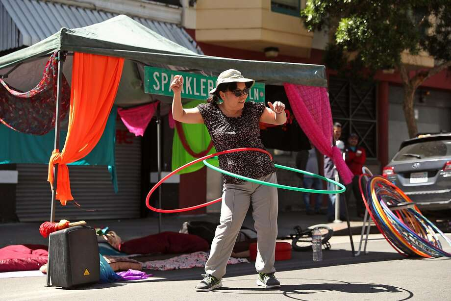"""Jennifer Chung hula-hoops at the """"Giant Puppets Save the World"""" booth. Photo: Scott Strazzante, The Chronicle"""