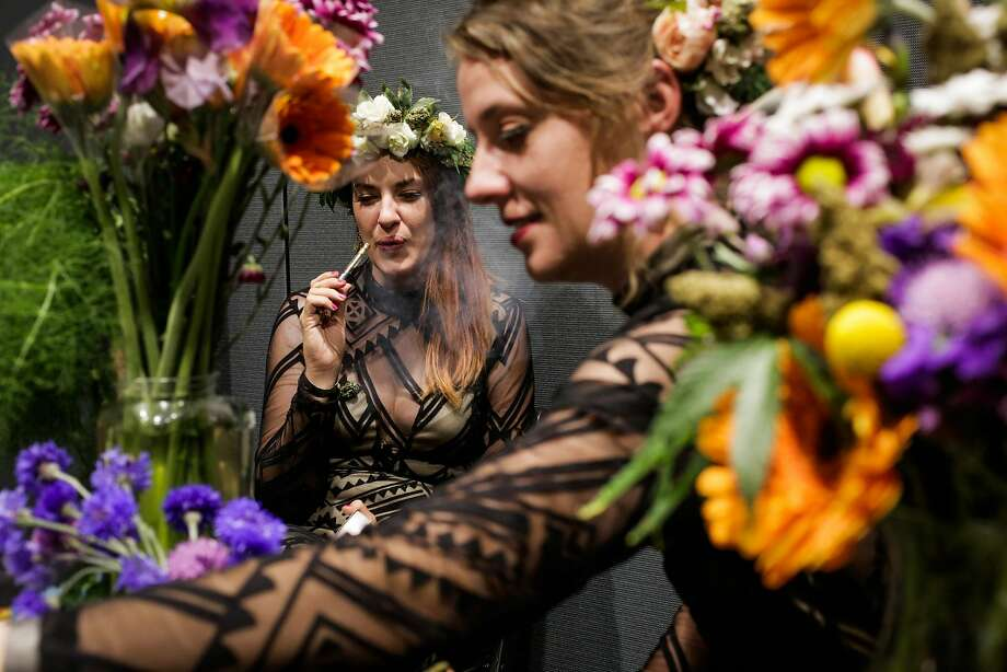 Leslie Monroy, owner of Flowers on Flowers, which offers floral wreaths and arrangements laced with marijuana buds, smokes while she and Xan Robinson work at the Cannabis Wedding Expo in S.F. Photo: Gabrielle Lurie, The Chronicle