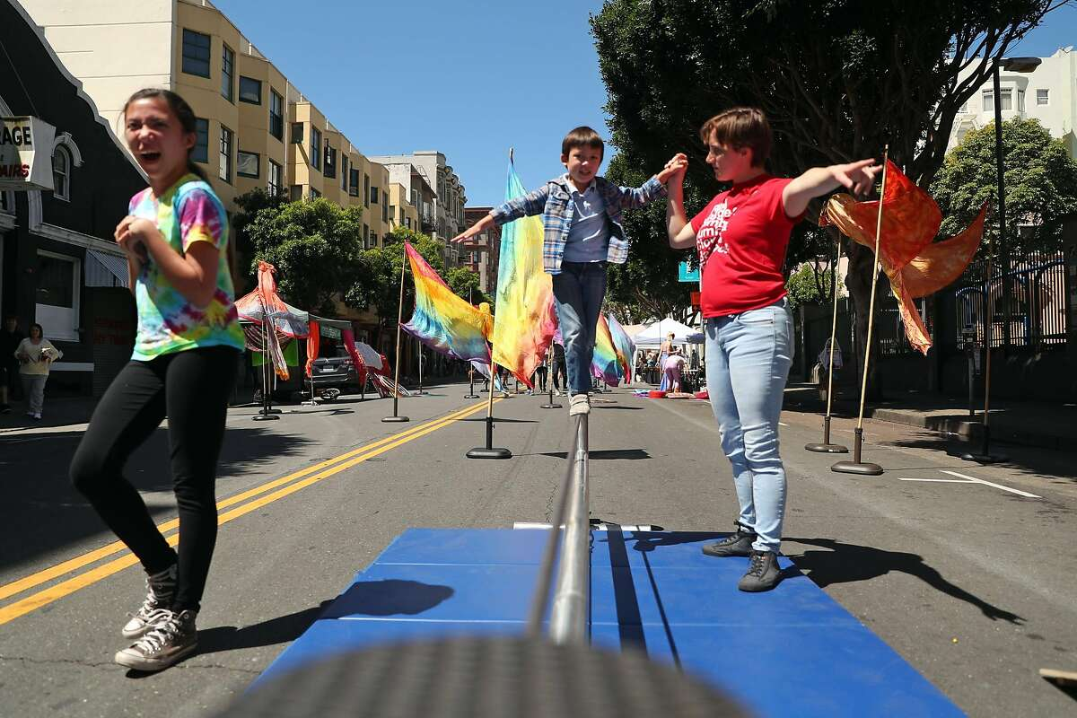 Circus Center's Phoenix Paz helps Elliott Dumant, 5, on a tight rope as his sister Ella, 13, laughs during Sunday Streets in The Tenderloin on Ellis Street in San Francisco, Calif., on Sunday, April 30, 2017.