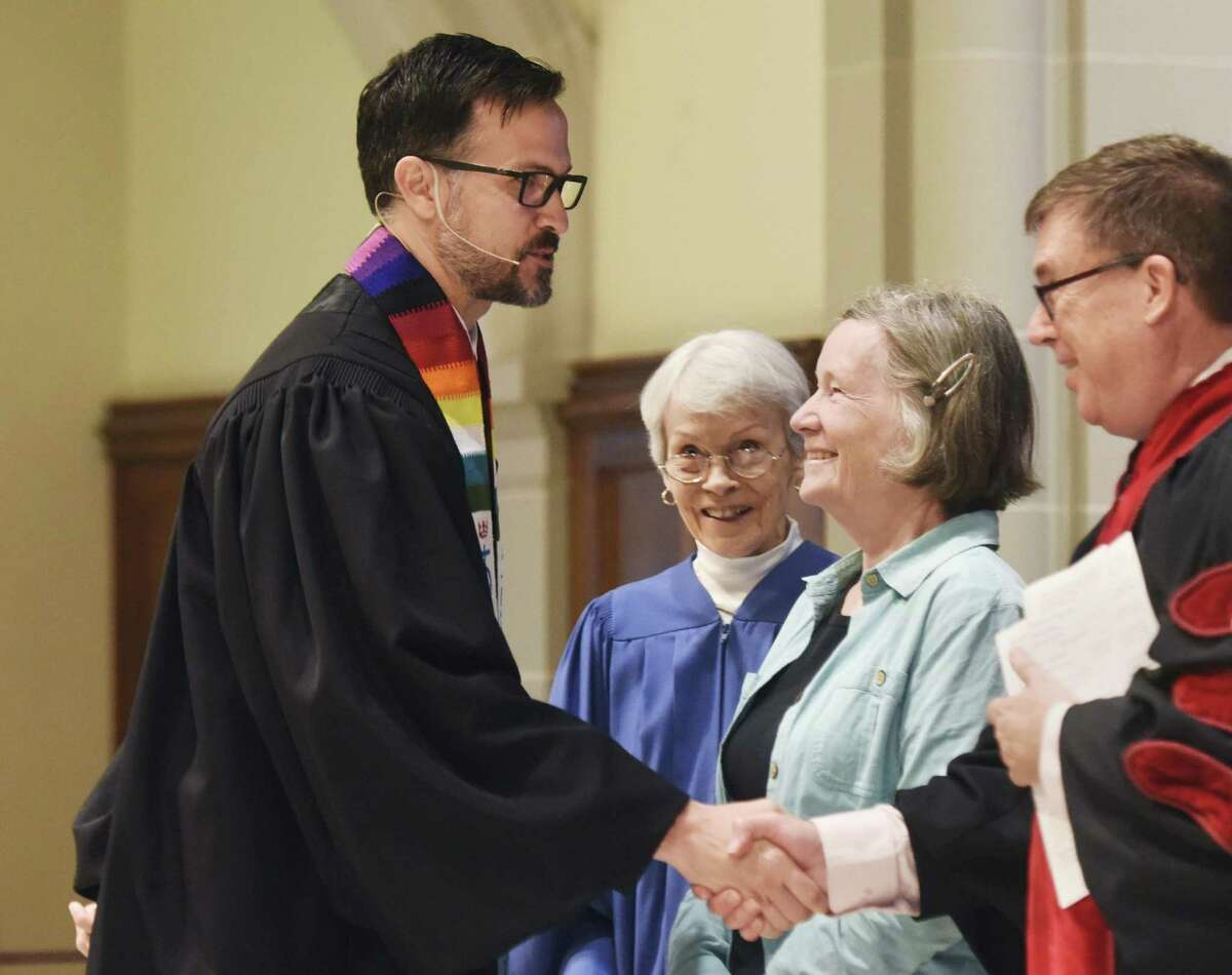 The Rev. Patrick Collins, left, Associate Pastor for Children, Youth and Families, is congratulated after being installed as a minister at First Congregational Church of Greenwich in Old Greenwich, Conn. Sunday, April 30, 2017. The Rev. Collins has emphasised a
