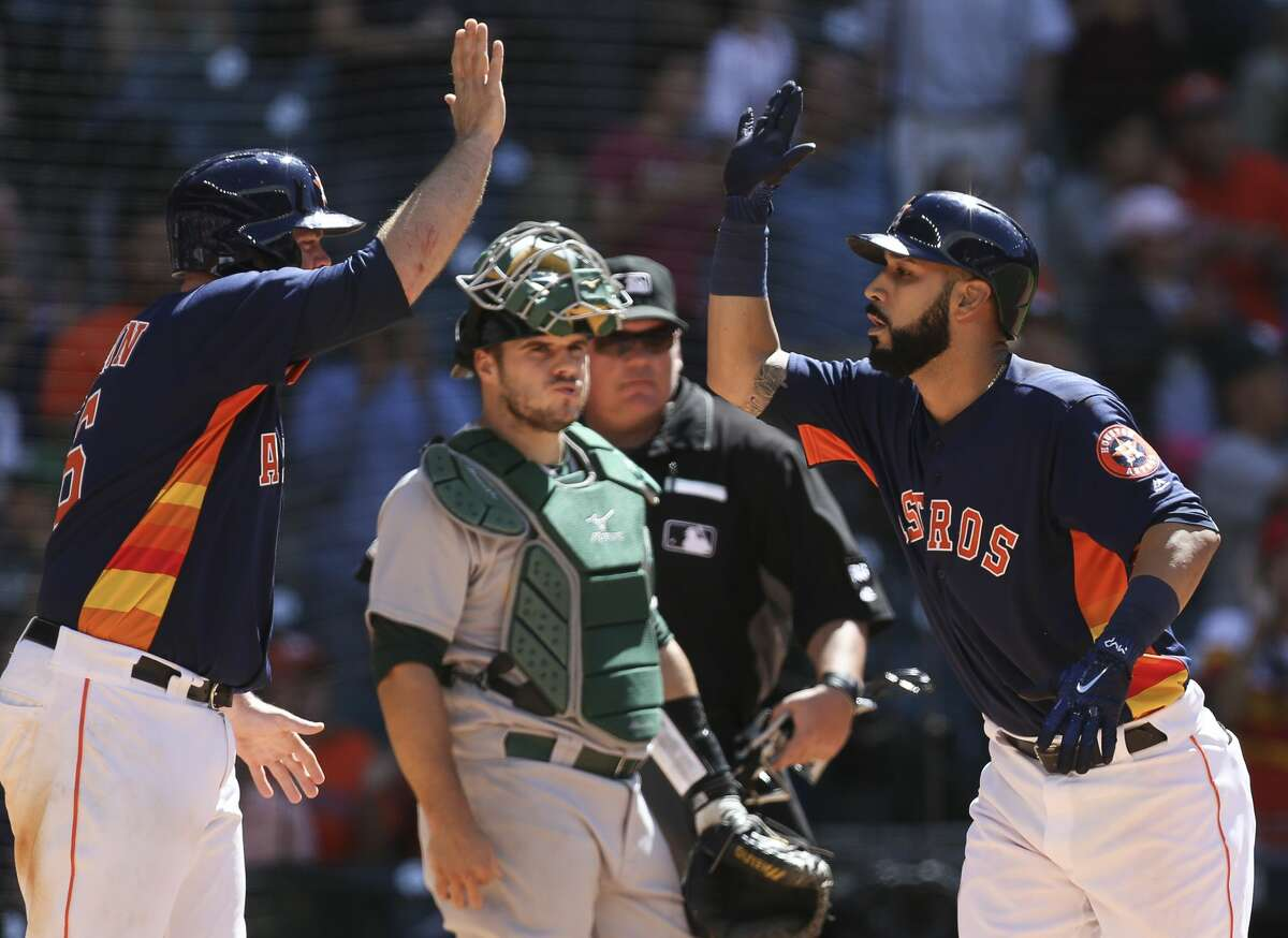 Houston Astros first baseman Marwin Gonzalez (9) and Brian McCann (16) celebrate Gonzalez's three-run homerun as Oakland Athletics catcher Josh Phegley (19) watches during the eighth inning of the game at Minute Maid Park Sunday, April 30, 2017, in Houston. ( Yi-Chin Lee / Houston Chronicle )
