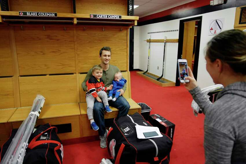 Erika Camper takes a photo of her husband, Albany Devils player, Carter Camper and their children, Brayden, 3, and Wyatt, 2 months, in the locker room at the Times Union Center on Sunday, April 30, 2017, in Albany, N.Y. (Paul Buckowski / Times Union)