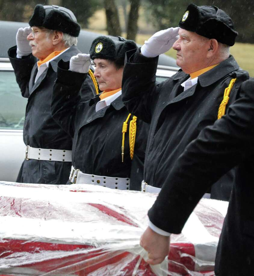 Members of the Saratoga National Cemetery honor guard, from left, Evan Hendricks, Caroline Sirchia and Joe Wright salute the flag draped coffin of Patrick Lee of Schenectady during his military funeral Thursday March 10, 2016 in Saratoga, NY.   (John Carl D'Annibale / Times Union) Photo: John Carl D'Annibale / 10035793A