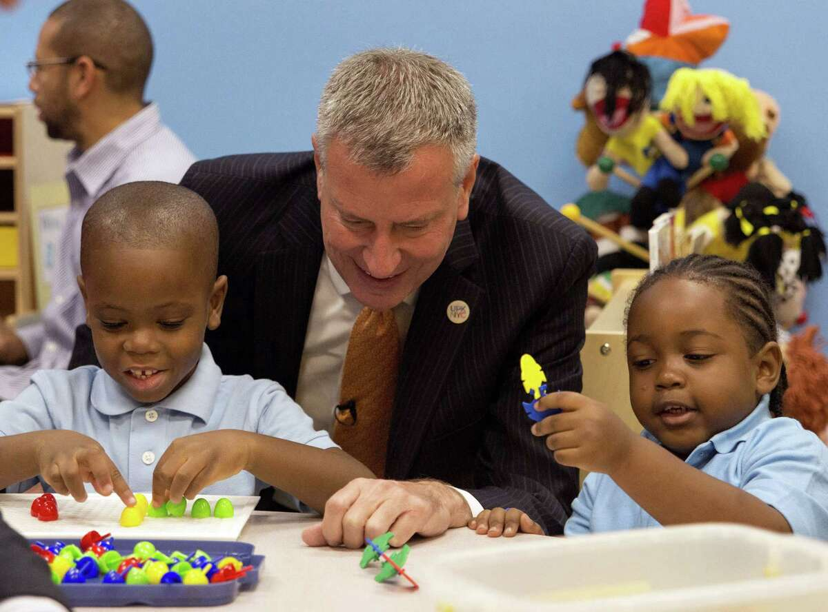 FILE - In this Sept. 4, 2014, file photo, New York Mayor Bill de Blasio visits the Inner Force Early Tots Childhood Learning Center, a community-based organization that's part of the pre-K program, in the Brooklyn borough of New York on the first day of the mayor's expansion of early childhood education. Free school for 4-year-olds was de Blasio's signature issue during his successful run for mayor in 2013. Facing re-election he has announced an ambitious plan to expand the effort to 3-year-olds. (Theodore Parisienne/The Daily News via AP, Pool, File) ORG XMIT: NYNYD501