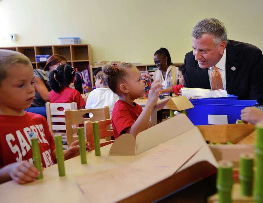 FILE - In this Sept. 4, 2014, file photo, New York Mayor Bill de Blasio and his wife, Chirlane McCray, center, visit a pre-kindergarten class on at the Sacred Heart School in the Staten Island borough of New York on the first day for the city's public schools and the first day of the mayor's expansion of early childhood education. Free school for 4-year-olds was de Blasio's signature issue during his successful run for mayor in 2013. Facing re-election he has announced an ambitious plan to expand the effort to 3-year-olds. (Susan Watts/The Daily News via AP, Pool, File) ORG XMIT: NYNYD502