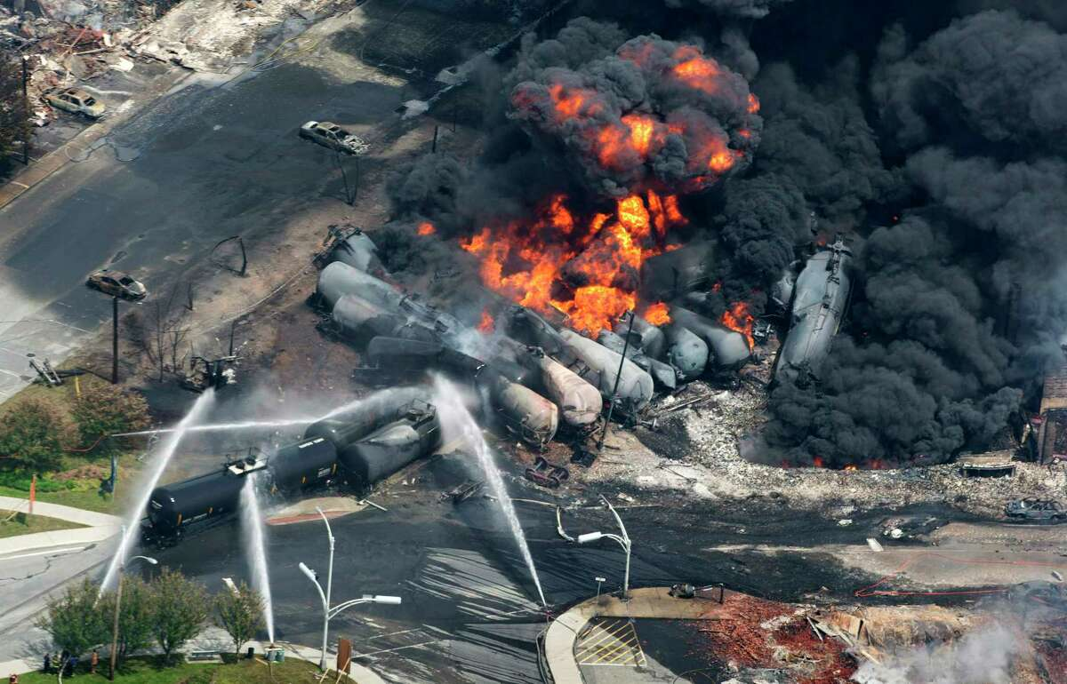In this Saturday, July 6, 2013 photo, smoke rises from railway cars carrying crude oil after derailing in downtown Lac Megantic, Quebec. Lac-Megantic still struggles to recover as it marks the disaster's one-year anniversary. (AP Photo/The Canadian Press, Paul Chiasson) ORG XMIT: CPT106