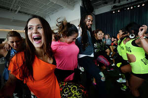 """Raquel Ellie Ibarra (left) and others join in a spirited group dance during the """"Set the Floor on Fiah"""" Zumba fitness concert at the Event Centre in Beaumont Sunday. Famous performer Watatah Fiah (center) & DJ Mauricio kept the beats pounding as zumba enthusiasts danced their way to fitness. Proceeds from the event benefitted Child Abuse and Forensic Services, a non-profit organization that treats and offers legal services for abused children and victims of sexual assault. Photo taken Sunday, April 30, 2017 Kim Brent/The Enterprise"""