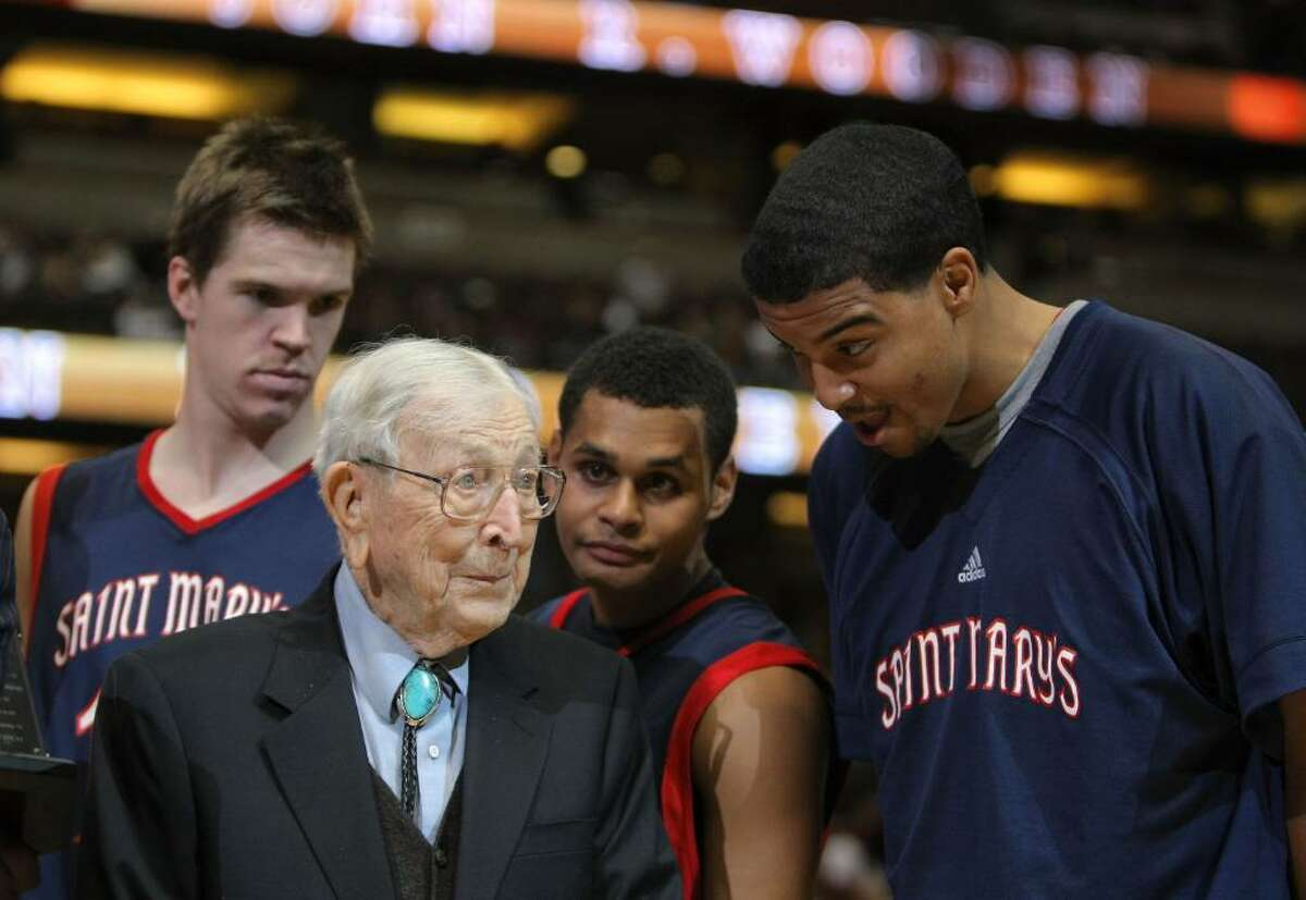 ANAHEIM, CA - DECEMBER 08: John Wooden chats with Yusef Smith #5, Patrick Mills #13 and Lucas Wlaker #12 of the St Mary's College Gaels after a 69-64 win over the San Diego State Aztecs during the John Wooden Classic at the Honda Center on December 8, 2007 in Anaheim, California. (Photo by Harry How/Getty Images)