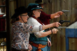 Women compete at the Texas State Cowboy Fast Draw Competition at Camp Waluta near Silsbee on Friday. Competitors dress in Wild West attire and compete to see who can draw and fire their pistols the quickest.  Photo taken Friday 4/28/17 Ryan Pelham/The Enterprise