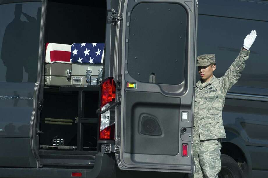 Air Force Senior Airman John Lee closes the door of the transfer vehicle con- taining the remains of Army Sgt. Joshua Rodgers, 22, of Bloomington, Ill., and Army Sgt. Cameron Thomas, 23, of Kettering, Ohio,  at Dover AFB. Photo: Cliff Owen / Associated Press / FR170079 AP