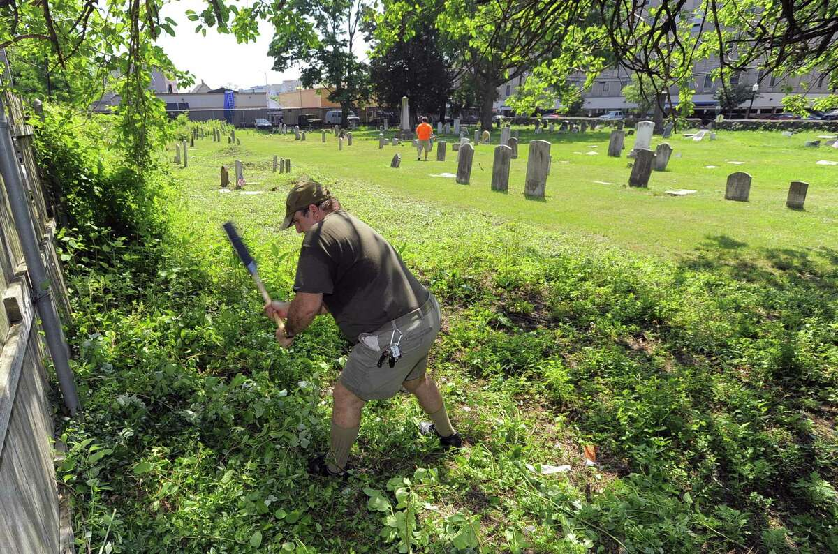 Phillip Peluso of Stamford, clears thick brush and over growth at Northfield Cemetery. Members of Greenwich's Acacia Lodge No. 85 and Stamford's Union No. 5 have been cleaning up the old burial ground at the corner of North and Franklin streets for years.