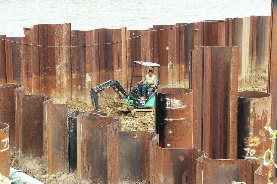 A construction worker digs close to the cofferdam with the Trinity River looming just feet away. The wall keeps the river out while construction for the new pump station goes on nearby. Photo: David Taylor