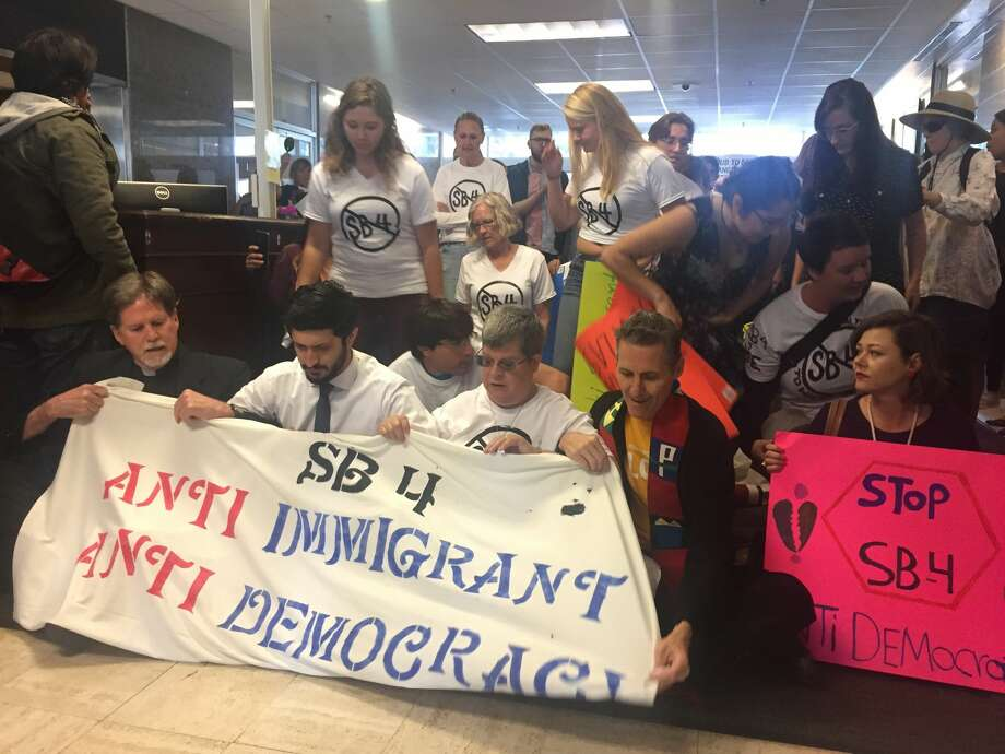Protestors host a sit-in at Texas Gov. Greg Abbott's office on May 1, 2017, in opposition of Senate Bill 4. Under the legislation, local law enforcement agencies and officials could be punished for failing to comply with federal immigration laws. Photo: Elena Lutz/San Antonio Express-News