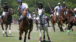 Team King Antonio's Ursula Pari MacLeod (center right) goes up against Team Austin's Ron Horne during the San Antonio Polo Club's Fiesta King Cup at Olmos Basin Park April 23.