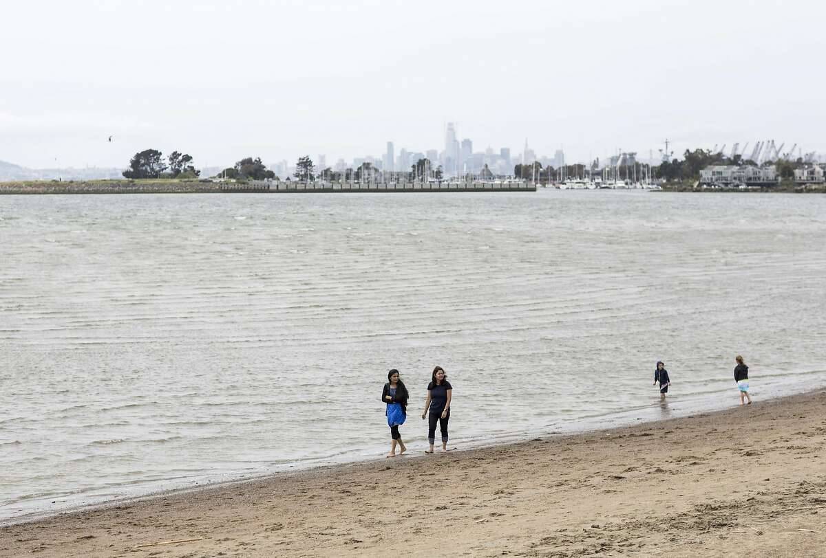 Visitors to the Robert W. Crown Memorial State Beach walk along the beach in Alameda, Calif., on Saturday, April 22, 2017. A kite surfer who was pulled from the water off Crown Memorial State Beach in Alameda died, officials said.