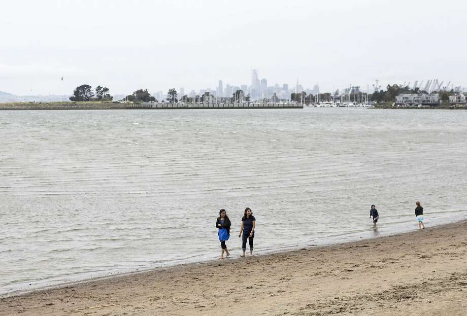 Visitors to the Robert W. Crown Memorial State Beach walk along the beach in Alameda, Calif., on Saturday, April 22, 2017. A kite surfer who was pulled from the water off Crown Memorial State Beach in Alameda died, officials said. Photo: Laura Morton, Special To The Chronicle