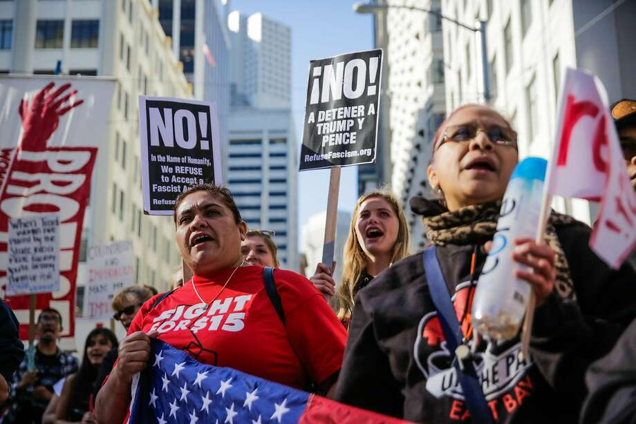 Veronica Gonzalez (left) and Miriam Cuevas (right) cheer as they protest immigration rights and fair pay outside of the U.S. Citizen and Immigration Services building on Sansome Street in San Francisco, California, on Monday, May 1, 2017. Photo: Gabrielle Lurie, The Chronicle