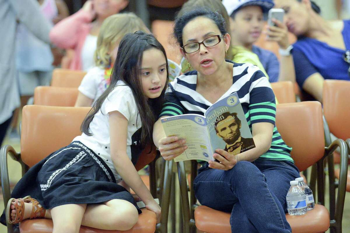 """Emily Iniguez, 7, and her mother Carmen Ortega, both of Stamford read together after picking out a selection of books during an event at the Ferguson Library in Stamfod, Conn. on April 29, 2017. The Stamford Public Education Foundation (SPEF) distributed free books and literacy resources to children in grades Pre-K through 5 at the biannual """"Reading is FUNdamental"""" book give-away. Approximately 300 to 400 children and adults attended this event and 600 to 800 books distributed. The event also included a collection of stories by professional storyteller, Laconia Therrio and arts and crafts activities."""