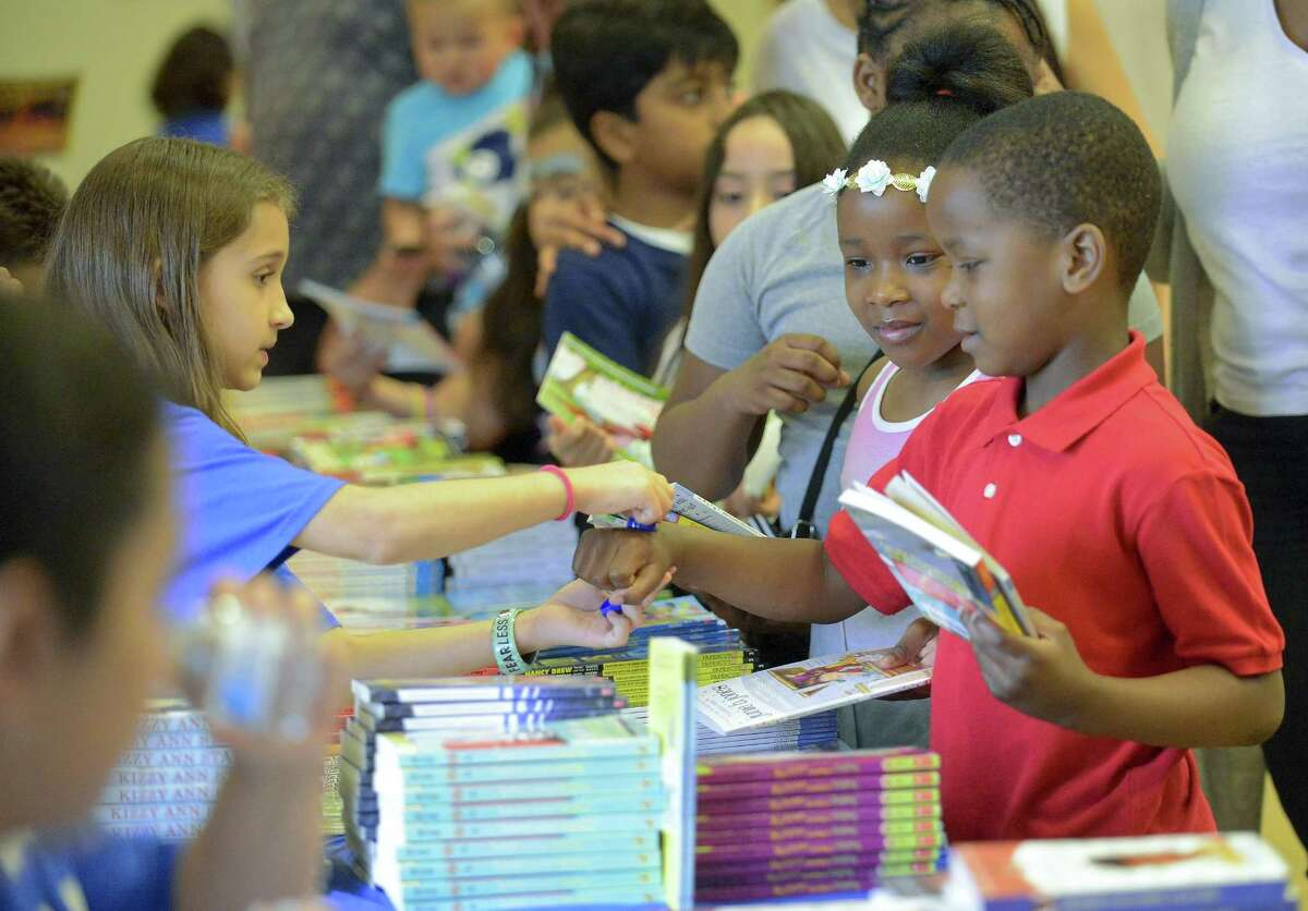"""At right, Olivia Beliard, 6, of Stamford watches as her twin brother Julien has his hand stamped after picking out books during an event at the Ferguson Library in Stamfod, Conn. on April 29, 2017. The Stamford Public Education Foundation (SPEF) distributed free books and literacy resources to children in grades Pre-K through 5 at the biannual """"Reading is FUNdamental"""" book give-away. Approximately 300 to 400 children and adults attended this event and 600 to 800 books distributed. The event also included a collection of stories by professional storyteller, Laconia Therrio and arts and crafts activities."""