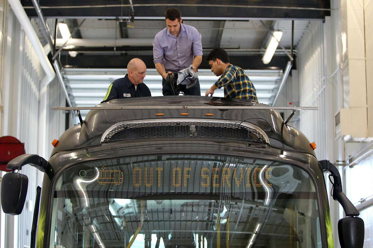 L to R Bill Lauer master mechanic with Regional Transportation Commission, works with Kostas Alexis assistant professor at University of Nevada Reno and graduate student Shehryar Khattak (cq) installing a string of cameras on top of a battery powered bus. Proterra, a Bay Area company that makes electric buses is doing a self-driving bus experiment jointly with researchers from the University of Nevada-Reno. Technicians equip a bus with the sensors for self-driving test, which includes cameras, and radar Monday, May 01, 2017. Monday, May 01, 2017. (Photo by Lance Iversen)