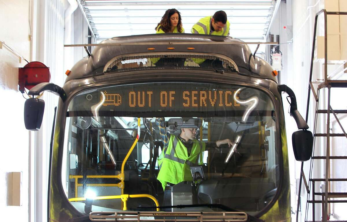 L to R Maria Tsiourva (cq) project coordinator works with Kostas Alexis assistant professor at University of Nevada Reno and inside the bus graduate student Shehryar Khattak (cq) are installing a string of hi definition cameras on top of a battery powered bus. Proterra, a Bay Area company that makes electric buses is doing a self-driving bus experiment jointly with researchers from the University of Nevada-Reno. Technicians equip a bus with the sensors for self-driving test, which includes cameras, and radar Monday, May 01, 2017. Monday, May 01, 2017. (Photo by Lance Iversen)