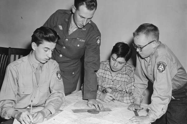 Plotting courses is part of the Civil Air Patrol ground school training for cadets. Here the group is plotting a mythical plane trip from Midland Airport to Musekgon. Shown are, from left, Cpl. Kendall Maursey, Warrant Officer Arnold Green, Pvt. Gerald Fetters and Pvt. Burr Corner. July 1950