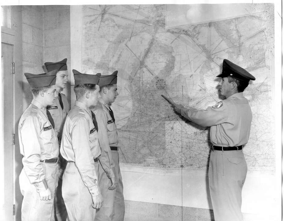 Civil Air Patrol L. J. Melstad, far right, squadron educational officer for the local group, instructs four cadets how to solve problems in map reading, The cadets are, from left, Bruce Henne, Donald Johnson, David Merritt and Mike Grinnell. December 1957 Photo: Daily News File Photo