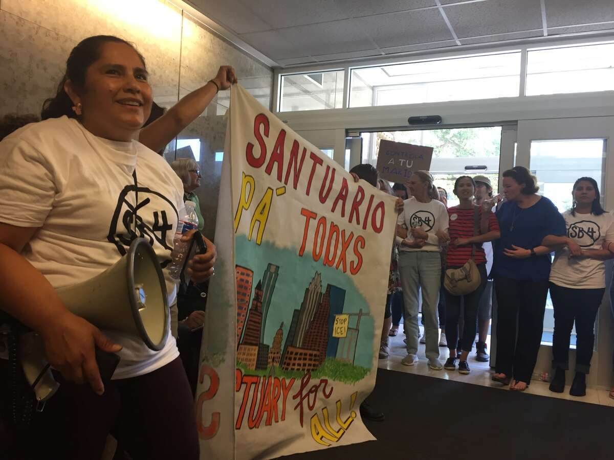 About 100 protesters chant in the lobby of the State Insurance Building in Austin Monday in hopes of convincing Gov. Greg Abbott to veto SB4, a bill that would allow law enforcement across the state to inquire about people's immigration at traffic stops and detain people the federal government wants to deport.