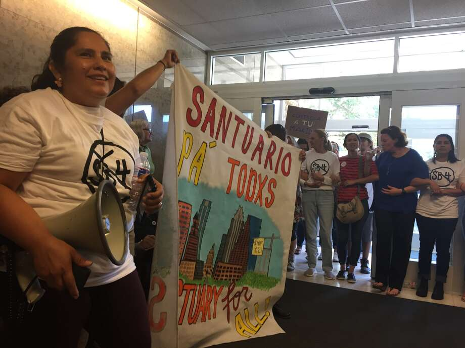 About 100 protesters chant in the lobby of the State Insurance Building in Austin Monday in hopes of convincing Gov. Greg Abbott to veto SB4, a bill that would allow law enforcement across the state to inquire about people's immigration at traffic stops and detain people the federal government wants to deport.  Photo: Andrea Zelinski, Houston Chronicle