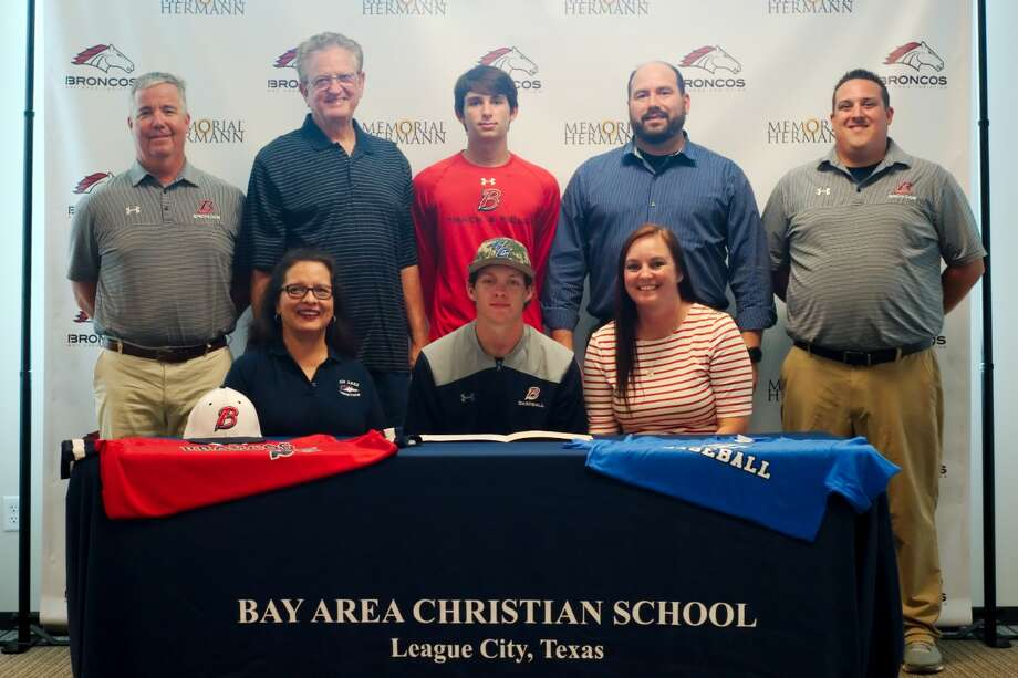 Bay Area Christian Athletic Director and baseball coach Kyle Kennedy, right, and assistant coach Jason Atwell stand with senior Christian Grigsby who is accompanied by his parents, David and Gina Hernandez and his grandparents, Ronald and Gina Gills as he signs a letter of Intent to attend Cisco Junior College to play baseball. Photo: Kirk Sides