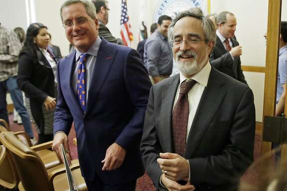 City Attorney Dennis Herrera, left, smiles while walking with San Francisco Supervisor Aaron Peskin, right, after announcing a settlement agreement on short term rentals during a news conference Monday, May 1, 2017, at City Hall in San Francisco. San Francisco and Airbnb have reached a deal to end a lawsuit over a law that fines the company for booking rentals not registered with the city. (AP Photo/Eric Risberg)
