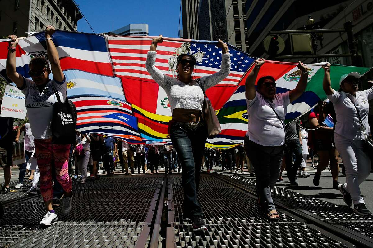 (L-R) Lisseth Sanchez and Natalie Mirena hold up a banner of flags in the air as she walks down Market Street during a May Day demonstration in San Francisco, California, on Monday, May 1, 2017.