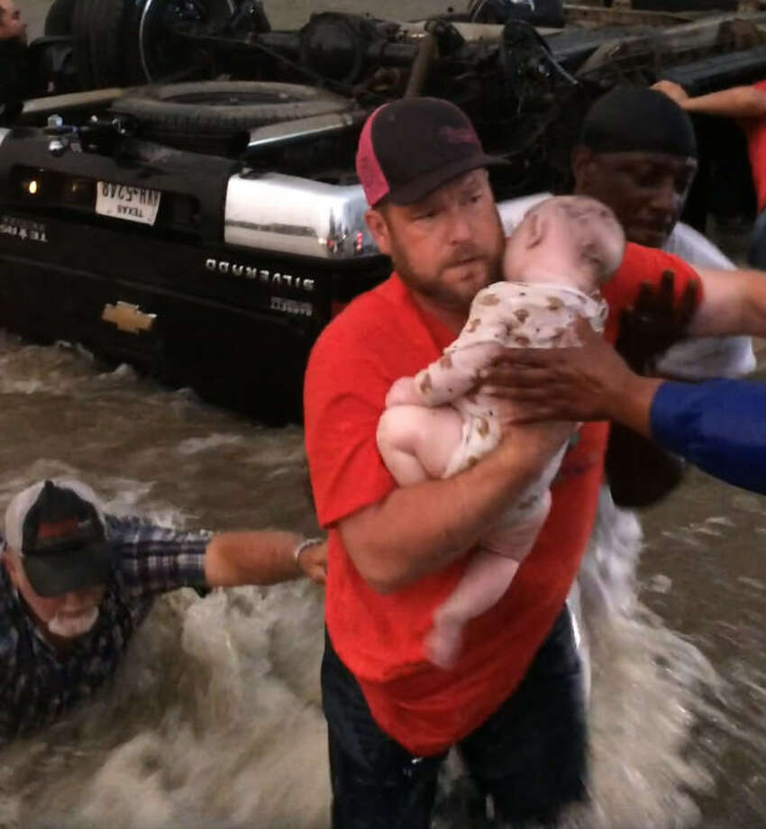 A group of good Samaritans gathered together to rescue two young children from an over-turned truck in Texas during the storms that shook North Texas during the last weekend of April in 2017. Source: Facebook Photo: Tom Mitchell Via Daid Schechter On Facebook